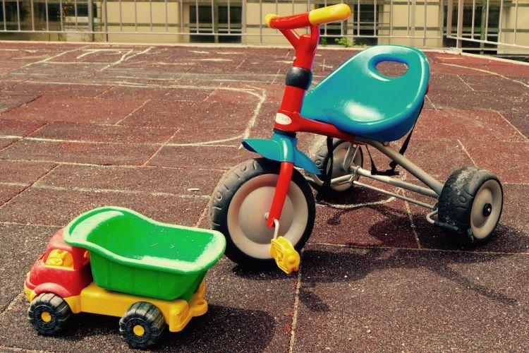 Den Kindern stehen verschiedene Spielgeräte wie Dreiräder oder Plastiklastwagen zur Verfügung.